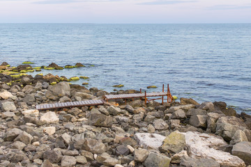 Wooden bridge to the sea. Ocean coast. Place of solitude. The path to the sea. The edge of the world. Stone beach. Fishing pier. Pier for boats. The coastline of the Black Sea.
