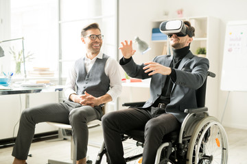 Young businessman sitting in wheelchair wearing virtual reality headset gesturing while his colleague watching for his actions