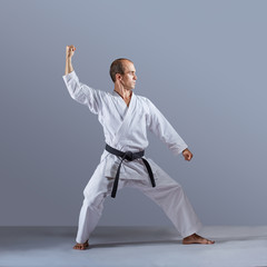 In karategi, an athlete trains formal karate exercises on gray background