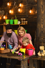 Father and son with mother. Flower care watering. Soil fertilizers. woman, man and little boy child love nature. happy gardeners with spring flowers. Family day. Greenhouse. Making me happy