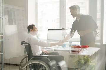 Businessman shaking hands with disabled man in wheelchair behind the window at office