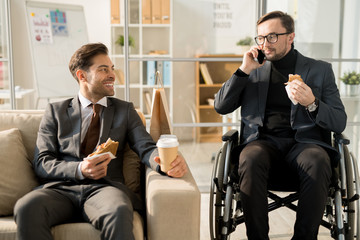 Young businessman sitting in wheelchair and talking on cellphone while has a lunch with his partner at office