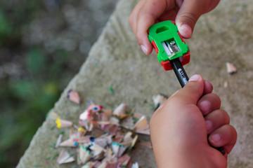 the kid sharpen a pencil. pencil. pen paste in the hand for school ,kindergarten, preschool activity concept.