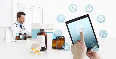 internet healthcare and medical on mobile devices consultation, hand touch screen on digital tablet with symbols, doctor at desk office with pills, drugs and medicine bottles