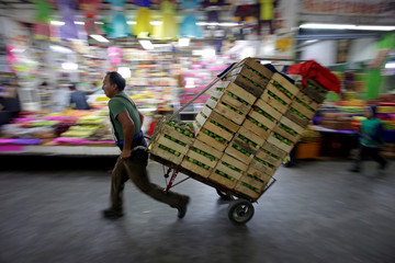 "A worker moves boxes with green tomatoes through the corridors of the wholesale market ""Central de Abastos"" in Mexico City"