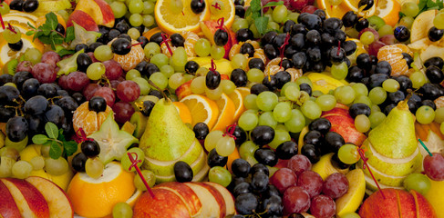 Assortment of healthy raw fruits, platter background, apple, pear, grapes, orange, mandarin, top view, selective focus