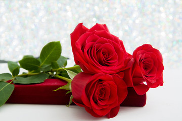 Three Red Roses and jewelery present box with boke Background. copy space - Valentines and 8 March Mother Women's Day concept.