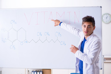 Young chemist standing in front of the whiteboard
