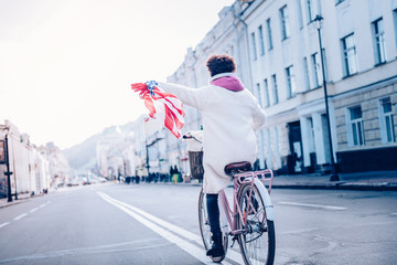 Cheerful international young woman demonstrating American flag
