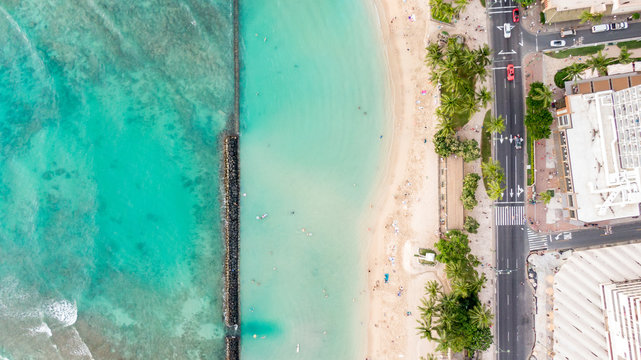 Stunning aerial drone view of Kuhio Beach, part of Waikiki Beach in Honolulu on the island of Oahu, Hawaii. The beach is protected from the ocean through a concrete wall, making it an ocean pool.