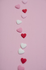 Flatlay with tiny heart-shaped sugar sprinkles in red, white and pink laid out in trace of trail as card for Valentine's Day on February 14th on wooden background, symbol of love and romantic feeling