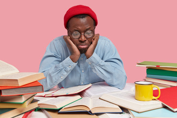 Upset black young man focused down, feels depressed and sad as reads books for long time, wears round spectacles, red hat and shirt, has dejected facial expression, isolated over pink studio wall
