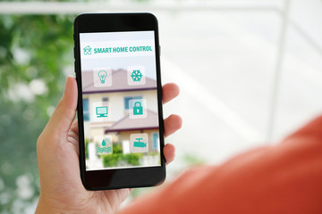 Hand holding smart phone with smart home control icon on screen device, smart home control concept