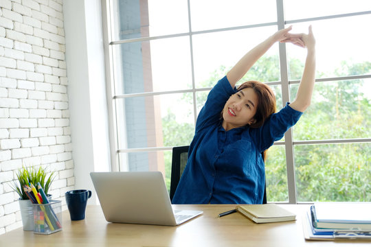Young asian woman stretching body for relaxing while working with laptop computer at her desk, home office lifestyle, business situation