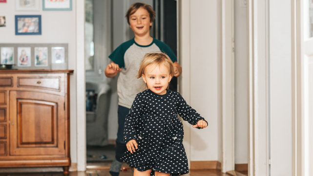 Two funny kids playing together at home, running and jumping