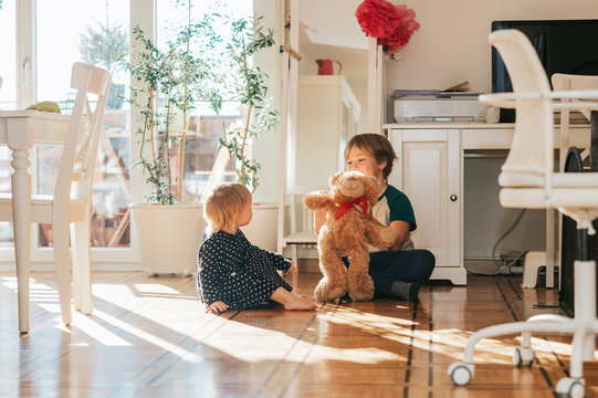 Two funny kids playing together with teddy bear at home in white living room filled with sunlight