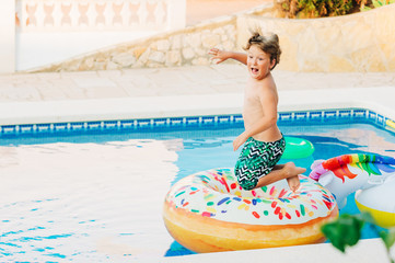 Funny little boy jumpping into the pool, summer activities for children
