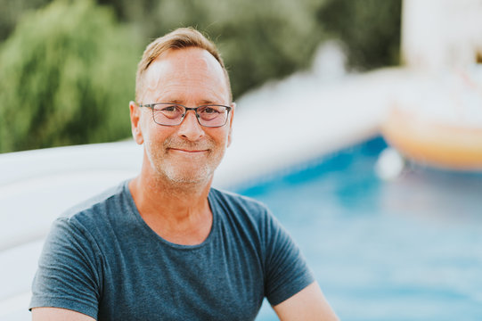 Outdoor portrait of 50 year old man resty by the pool, wearing blue t-shirt and glasses