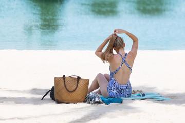Blonde tourist girl in bikini relaxed and sunbathing on the beach
