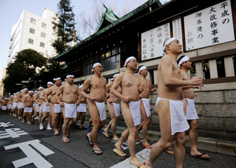 People wearing loin cloths  run to warm up before bathing in ice-cold water in a ceremony to purify their souls and wish for good health in the new year at the Teppozu Inari shrine in Tokyo