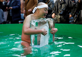 A man wearing loin cloth holds a brick of ice after bathing in ice-cold water in a ceremony to purify souls and wish for good health in the new year at the Teppozu Inari shrine in Tokyo