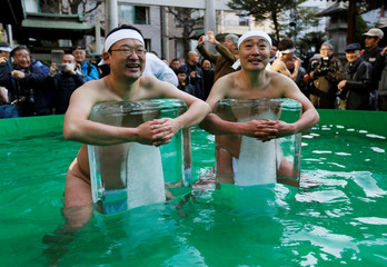 Men wearing loin cloth hold bricks of ice after bathing in ice-cold water in a ceremony to purify souls and wish for good health in the new year at the Teppozu Inari shrine in Tokyo