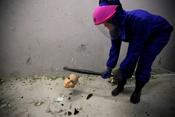 A female customer wearing protective gear smashes the head of a mannequin in an anger room in Beijing