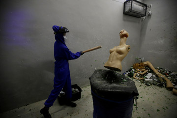 Female customer wearing protective gear smashes a mannequin in an anger room in Beijing