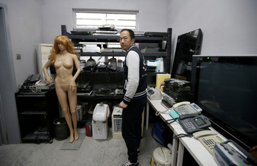 Manager of Anger Room 'Smash' Zhuo Hanjing stands next to old electronic devices and a mannequin, to be used for smashing by customers, in Beijing