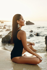 Woman On Beach. Girl In Black Swimsuit Sitting On Sea Coast