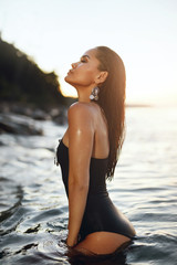 Woman Fashion And Summer Style. Girl In Black Swimsuit In Sea