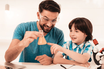 Youn Bearded Father Teaching Son in Shirt at Home.
