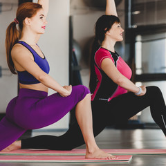 Two fit flexible women doing yoga exercise in studio