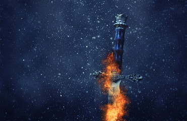 mysterious and magical photo of silver sword with fire flames over gothic snowy black background. Medieval period concept.