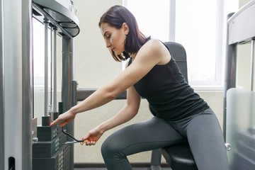 Young athletic woman exercising on the machines in modern sport gym. Fitness, sport, training, people, healthy lifestyle concept.