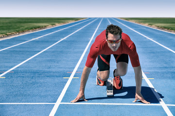 Sprinter athlete ready to start running race waiting at line on starting blocks on blue run tracks at outdoor stadium. Focus and motivation sport and fitness concept.