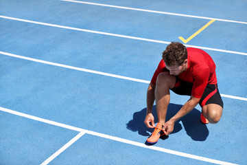 Athlete sprinter getting ready to run tying up shoe laces on stadium running tracks. Man runner preparing for race marathon training outdoors. Fitness and sports.