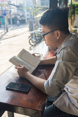 Vertical photo of Asian man reading book in the coffee time