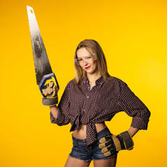 Young playful woman in jeans and plaid shirt holding hand saw