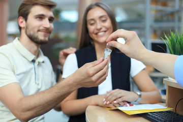Close up of real estate agent giving keys to couple of customers.