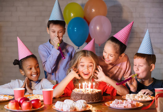 Kids looking at birthday cake with candles