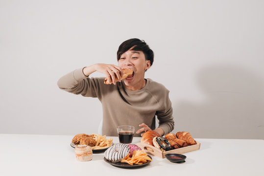 Portrait of asian man sitting and snacking donuts isolated over white background. Fat man diet concept