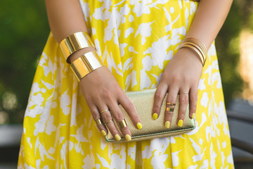 Unrecognizable woman holding wallet in her hands. Lady`s hands wearing rings and accessiories. Girl in yellow dress