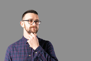 Young handsome man with facial hair holding posing over gray wall with a lot of copy space for text. Portrait of confident bearded male, wearing hipster slim fit checkered shirt. Isolated, background.