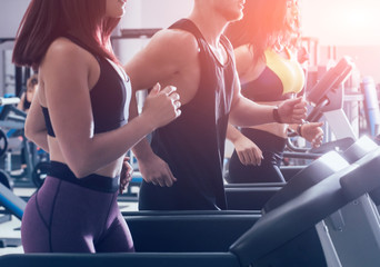Young peoples training on treadmill at the gym. In fitness center. Fototapete