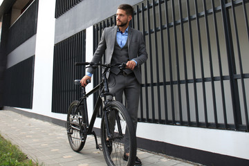 Confident young businessman standing with bicycle on the street in town.