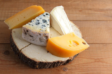 Assortment of cheeses on wooden boards. Camembert, hard yellow cheese, dorblu on wooden stand. Top view