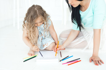 Young mother and her little daughter playing together. Family drowing with colorful pencils