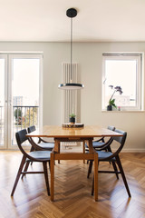 Stylish and cozy dining room interior with design family table, chairs and lamp. Big sunny windows, white and yellow marble walls and brown wooden parquet. Modenr space.