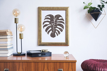 Retro and minimalistic interior with gold mock up poster frame on the vintage brown shelf, hanging plant in design pot, books, platns, table lamp and box.